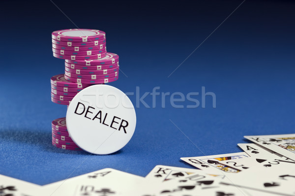 Dealer button with poker chips and playing cards on blue felt. Stock photo © Habman_18