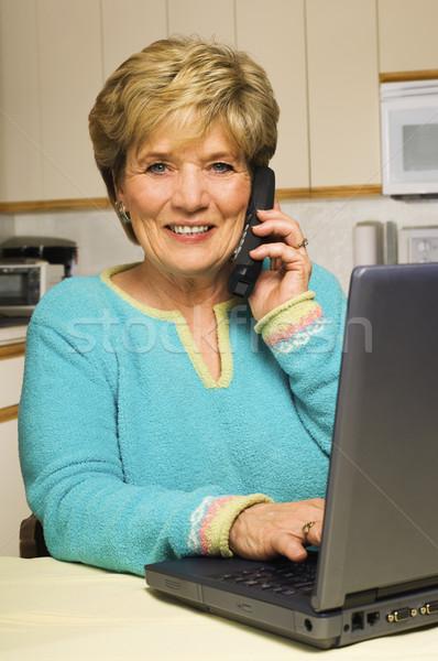 Woman talks on phone while working on laptop Stock photo © Habman_18