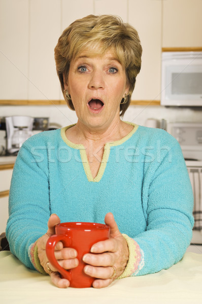 Senior woman, holding a coffee mug in her kitchen, with a look of surprise Stock photo © Habman_18