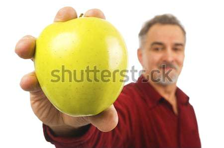 Mature man holds an apple by its stem Stock photo © Habman_18
