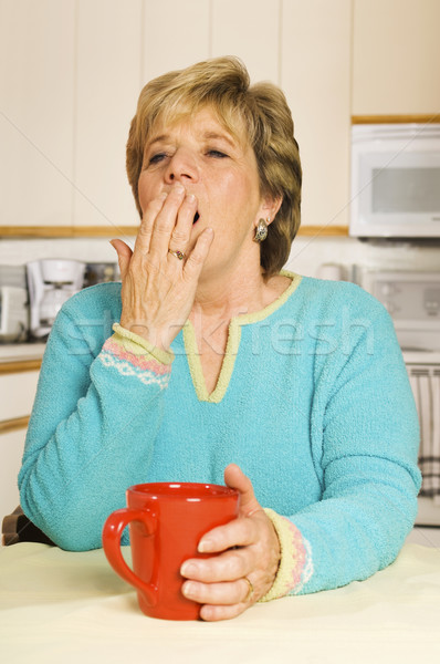 Yawning woman with red coffee mug in her kitchen Stock photo © Habman_18