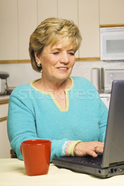 A senior woman works on her laptop in her kitchen, coffee mug at Stock photo © Habman_18