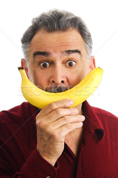 Man holding banana to face, imitating smile Stock photo © Habman_18