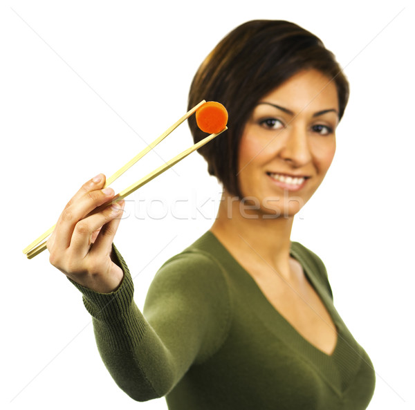 Young happy woman holds a carrot slice with chopsticks Stock photo © Habman_18