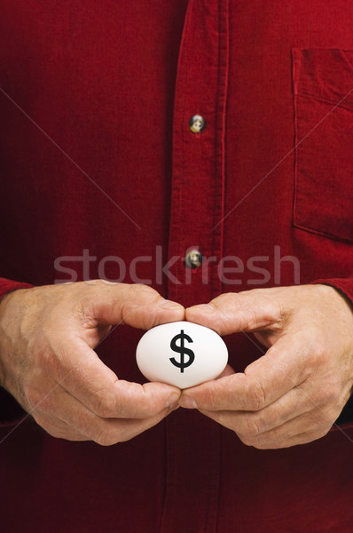 Dollar sign ($) written on egg held by man Stock photo © Habman_18
