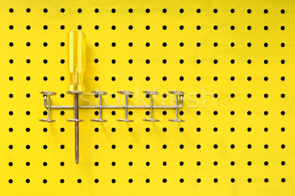 One yellow screwdriver sits in a rack on a pegboard Stock photo © Habman_18