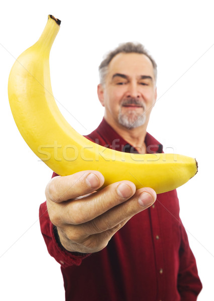 Man offers a yellow banana with outstretched arm Stock photo © Habman_18