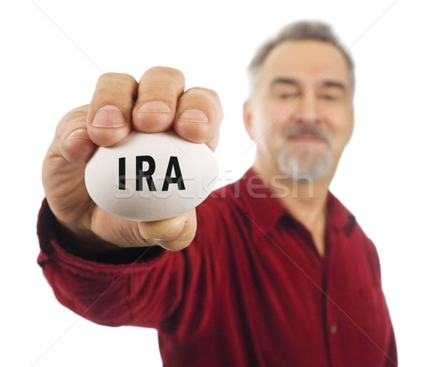 Mature man holds an egg with IRA on it. Stock photo © Habman_18