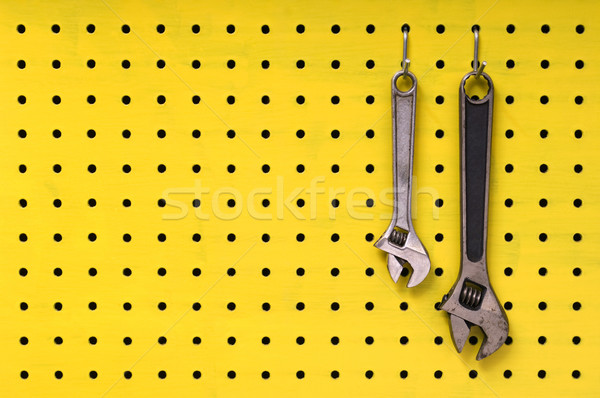 Two wrenches hang from hooks on yellow pegboard Stock photo © Habman_18