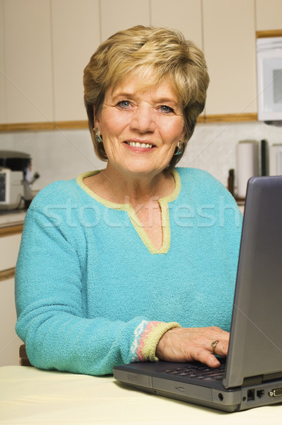 Woman works on laptop in kitchen Stock photo © Habman_18