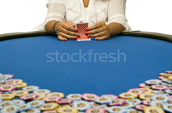 Stock photo: Woman holding playing cards on blue felt table with chips in for