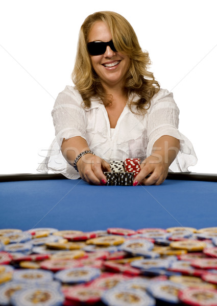 Stock photo: Woman pushes poker chips on blue felt table