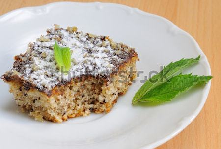 Sweet cake (gingerbread) with chocolate icing, nuts and small mint leaf.  Stock photo © hamik