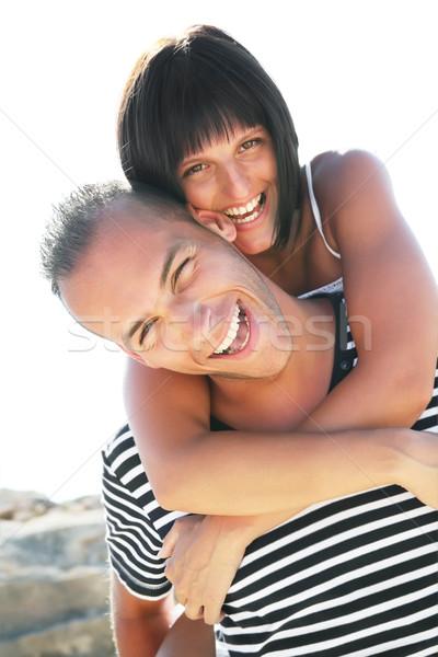 Smiling young couple having fun at the beach Stock photo © hannamonika