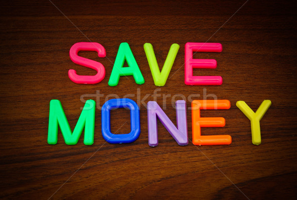 Save money in colorful toy letters on wood background  Stock photo © happydancing