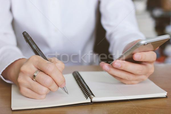 Vrouw handen smartphone schrijven notebook kantoor Stockfoto © happydancing