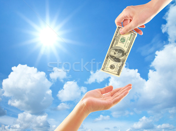 Hand giving money to other hand over clouds and sun Stock photo © happydancing
