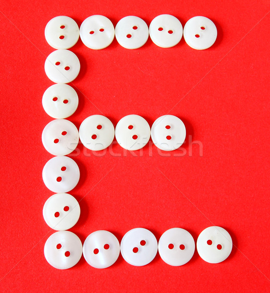 Letter 'E' from buttons on a red background  Stock photo © happydancing