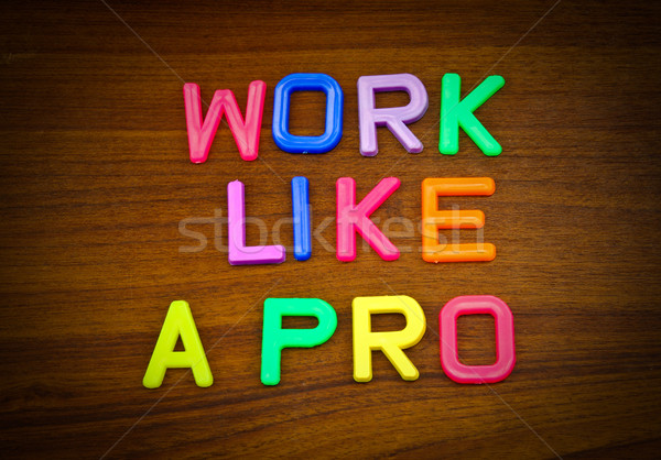 Work like a pro in colorful toy letters on wood background  Stock photo © happydancing