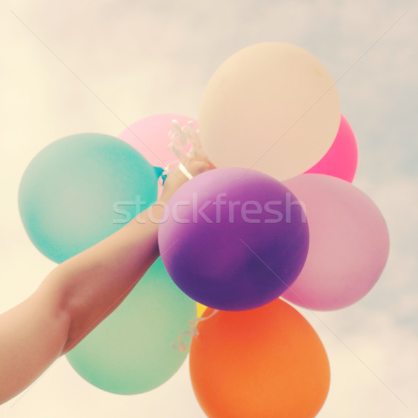 Hand holding multicolored balloons with retro filter effect  Stock photo © happydancing