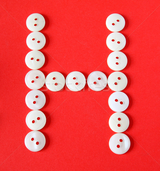 Letter 'H' from buttons on a red background  Stock photo © happydancing