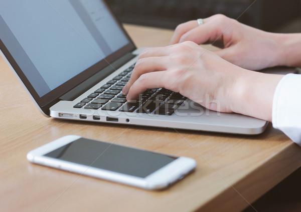 Vrouw typen laptop smartphone tabel kantoor Stockfoto © happydancing