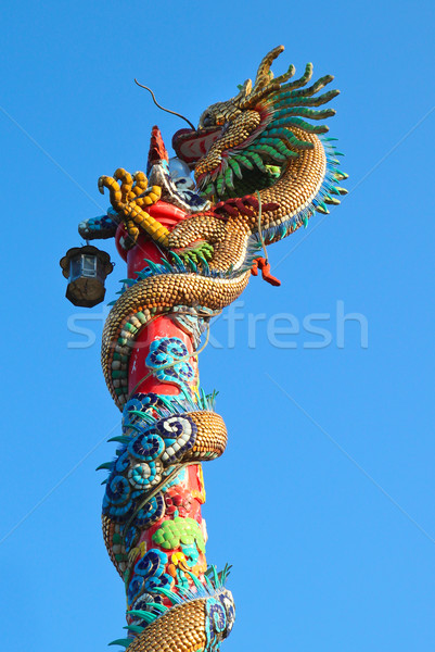 Golden dragon statue on red pillar against blue sky Stock photo © happydancing