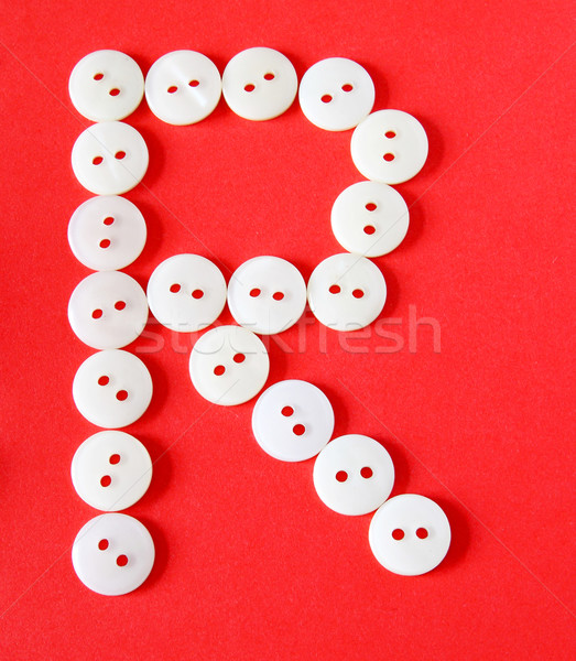 Letter 'R' from buttons on a red background  Stock photo © happydancing