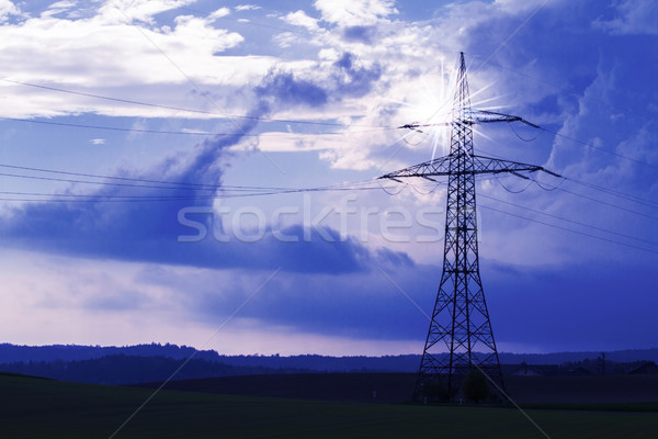 Stock photo: Electrical tower with sun rays and dramatic sky