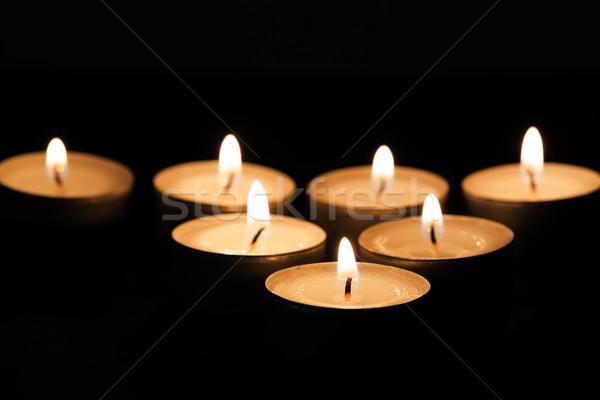 Burning tealights in darkness Stock photo © haraldmuc