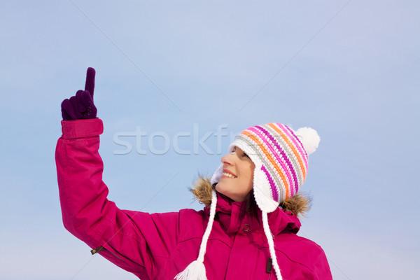 Pretty girl in witer clothes pointing upwards Stock photo © Harlekino