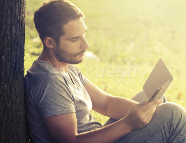 Młody człowiek czytania ebook drzewo komputera Internetu Zdjęcia stock © hitdelight