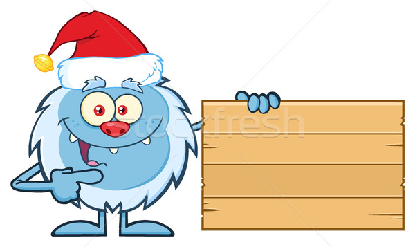 Little Yeti Cartoon Mascot Character With Santa Hat Pointing To A Wooden Blank Sign Stock photo © hittoon