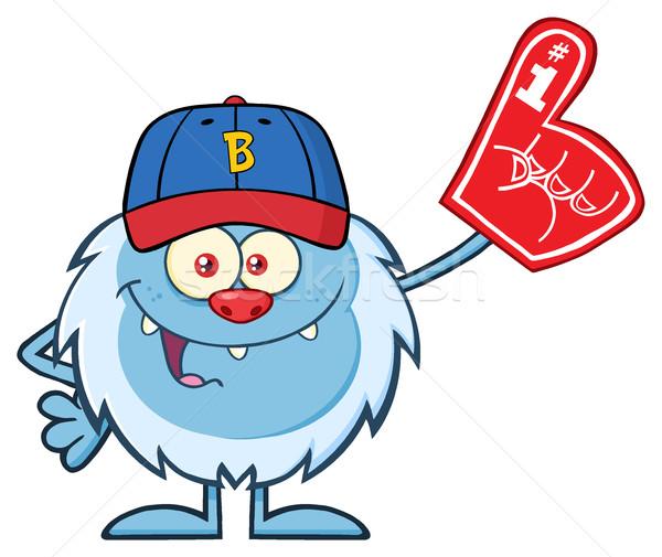 Happy Little Yeti Cartoon Mascot Character With Baseball Hat Wearing A Foam Finger Stock photo © hittoon