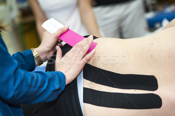 Massaging of young woman - kinesiotaping Stock photo © Hochwander
