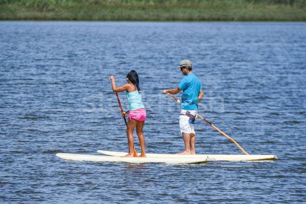 Man and woman stand up paddleboarding Stock photo © homydesign