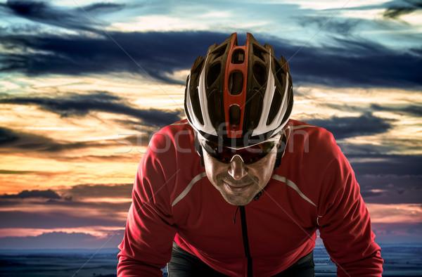 Ciclista casco nublado puesta de sol cielo carretera Foto stock © homydesign