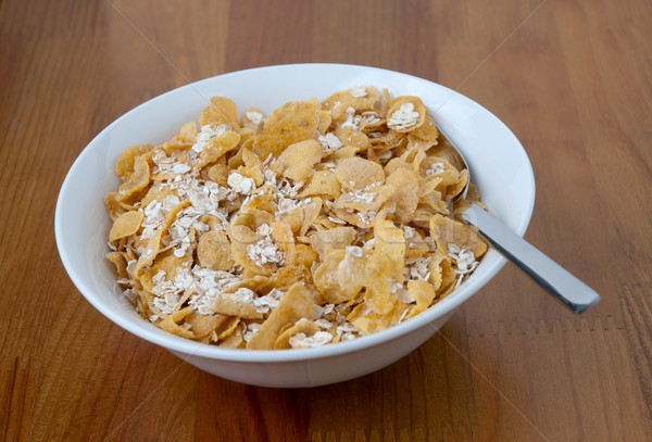 White bowl with a spoon, corn and oats flakes Stock photo © homydesign