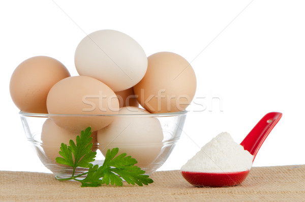 Brown eggs on brown and red ceramic spoon with white powder Stock photo © homydesign