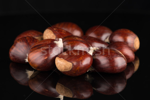 Chestnuts on a black reflective background Stock photo © homydesign