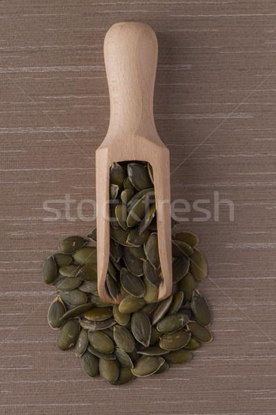 Wooden scoop with pumpkin seeds Stock photo © homydesign