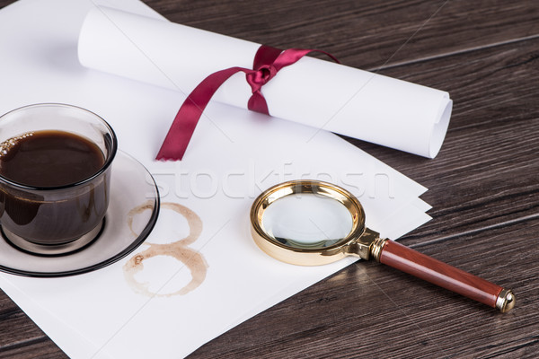 Coffee cup, paper sheets and detective magnifying glass Stock photo © homydesign