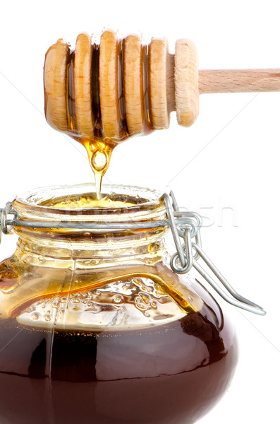 Jar of honey with wooden drizzler Stock photo © homydesign