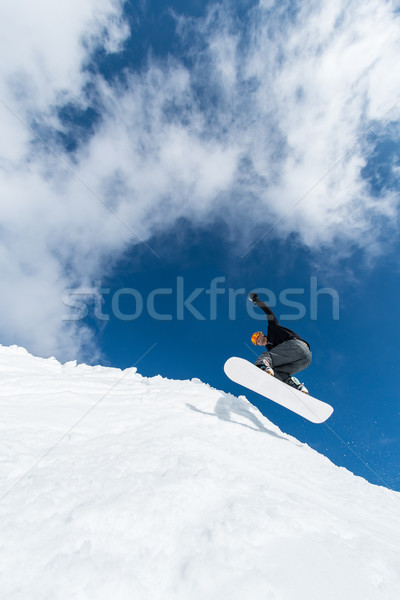 Snowboarder jumping against blue sky Stock photo © homydesign