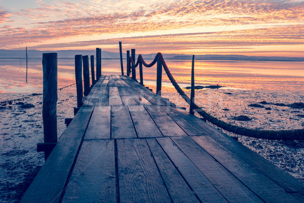 Sunrise of a wooden pier Stock photo © homydesign