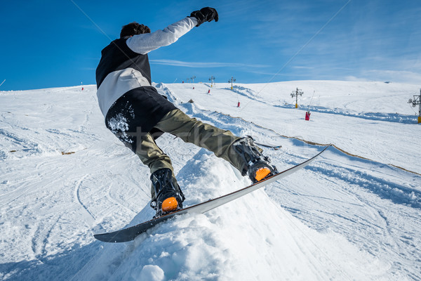 Snowboarder sliding against blue sky Stock photo © homydesign