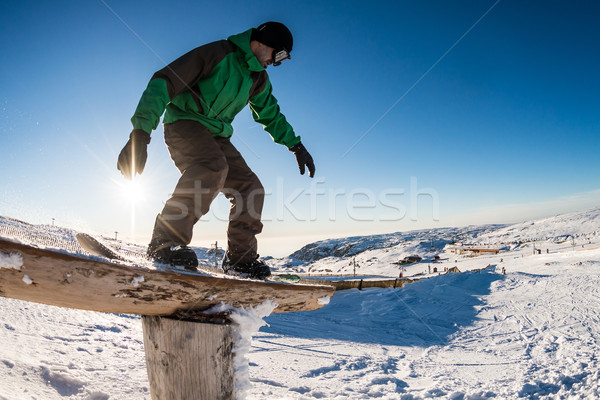 Snowboarder sliding on a rail Stock photo © homydesign
