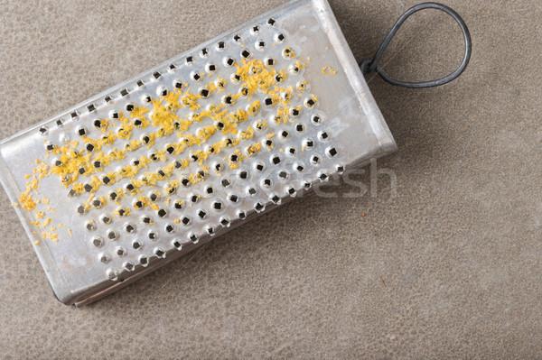 Metal scraper with lemon zest Stock photo © homydesign