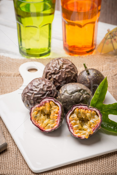 Passion fruits on white ceramic tray on wooden table background. Stock photo © homydesign