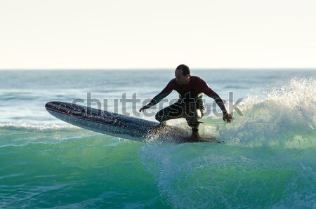 Long boarder surfing the waves at sunset Stock photo © homydesign